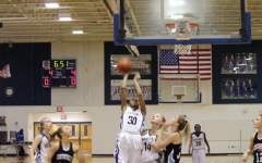 Varsity basketball player Ra'Sheika Gregory (center) scores at a home game against Centreville.