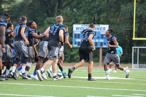 Football team members participate in a pep rally activity.