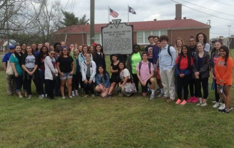 Students pose in front of the plaque commemorating the 1951 strike.