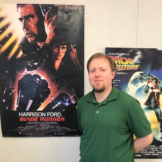 Mr. Reves pictured next to some of his many movie posters around his classroom.