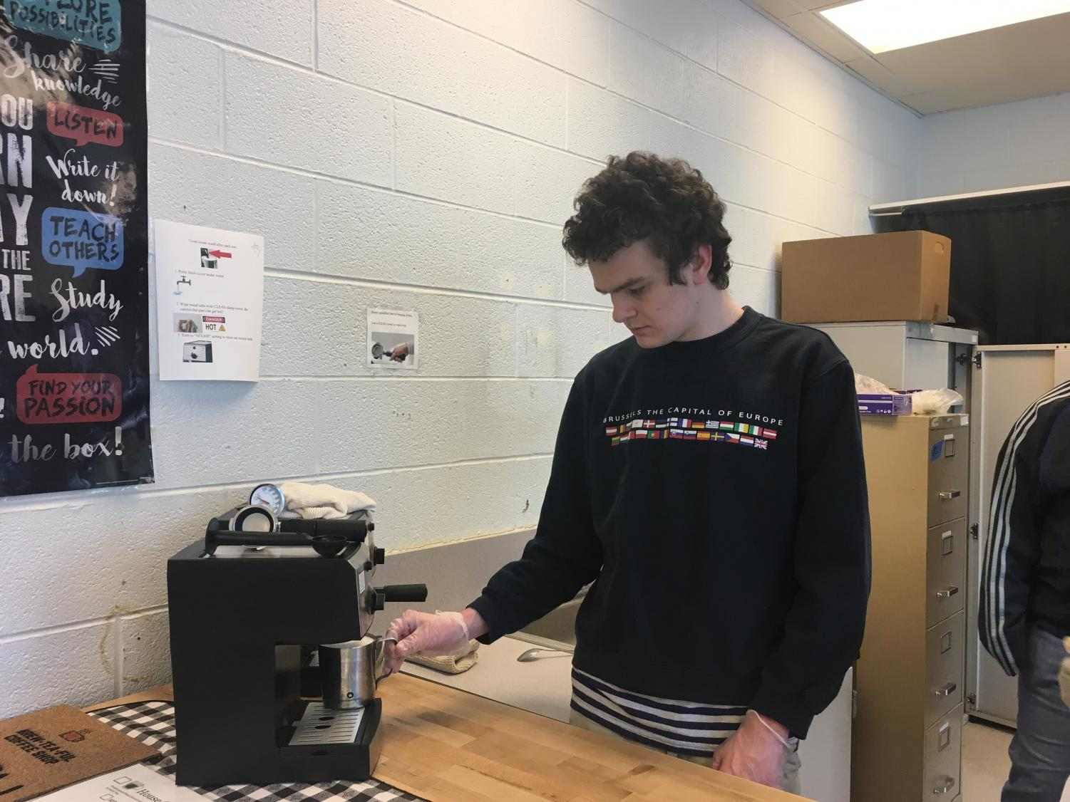 Collin Sproule, a Brew-Tea-Ful Coffee Shop employee, makes coffee for students during 7th period.